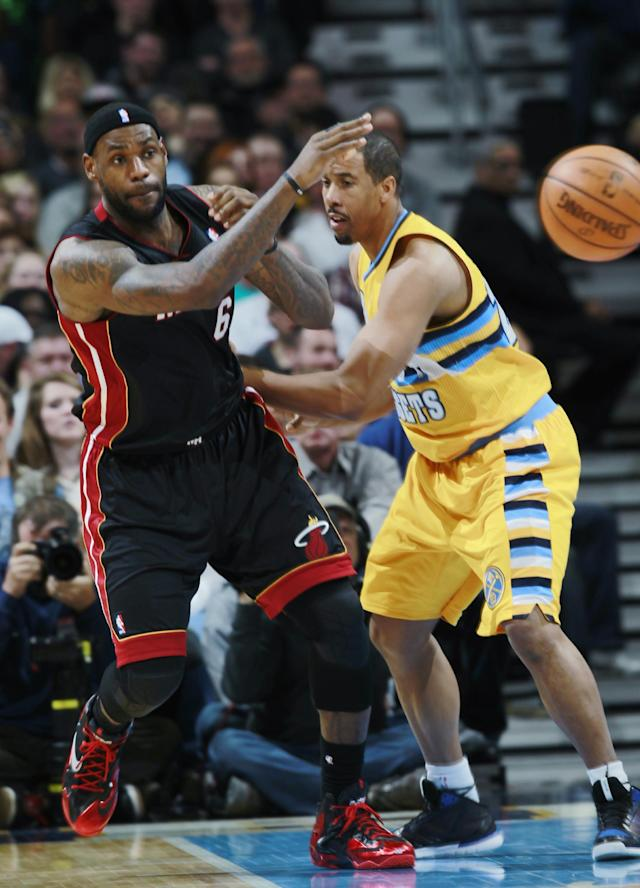 Miami Heat forward LeBron James, left, passes ball around Denver Nuggets guard Andre Miller in the fourth quarter of the Heat's 97-94 victory in an NBA basketball game in Denver on Monday, Dec. 30, 2013. (AP Photo/David Zalubowski)