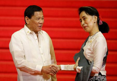 Philippine President Rodrigo Duterte shakes hands with Myanmar State Counsellor Aung San Suu Kyi before the start of the 30th ASEAN summit in Manila