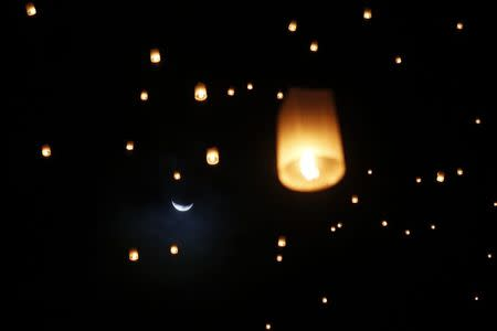The moon is seen behind lanterns released by survivors, local residents and visitors during the ceremony for victims of 2004 tsunami in Ban Nam Khem, a southern fishing village destroyed by the wave December 26, 2014. REUTERS/Athit Perawongmetha