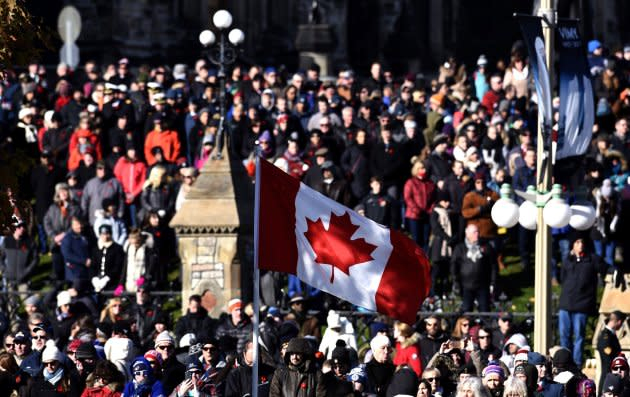 A Canadian flag flies as people line up along Wellington Street and outside Parliament Hill's East Block to watch the National Remembrance Day Ceremony.