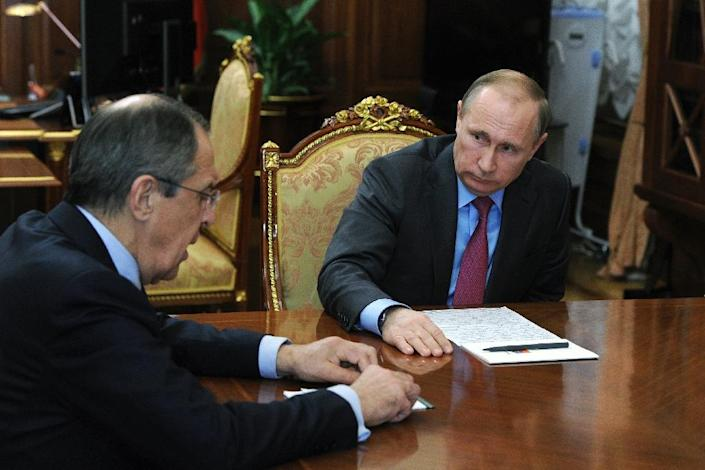 Russian President Vladimir Putin (R) meets with Defence Minister Sergei Shoigu (unseen) and Foreign Minister Sergei Lavrov (L) at the Kremlin in Moscow on March 14, 2016 (AFP Photo/Mihail Klimentyev)
