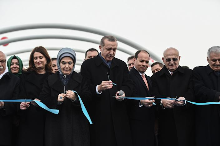 Turkish President Recep Tayyip Erdogan, center, with his wife Emine Erdogan by his side and Prime Minister Binali Yildirim, right, during the opening ceremony of a street tunnel under Bosphorus Street in Istanbul in December 2016. | Ozan Kose - AFP / Getty Images