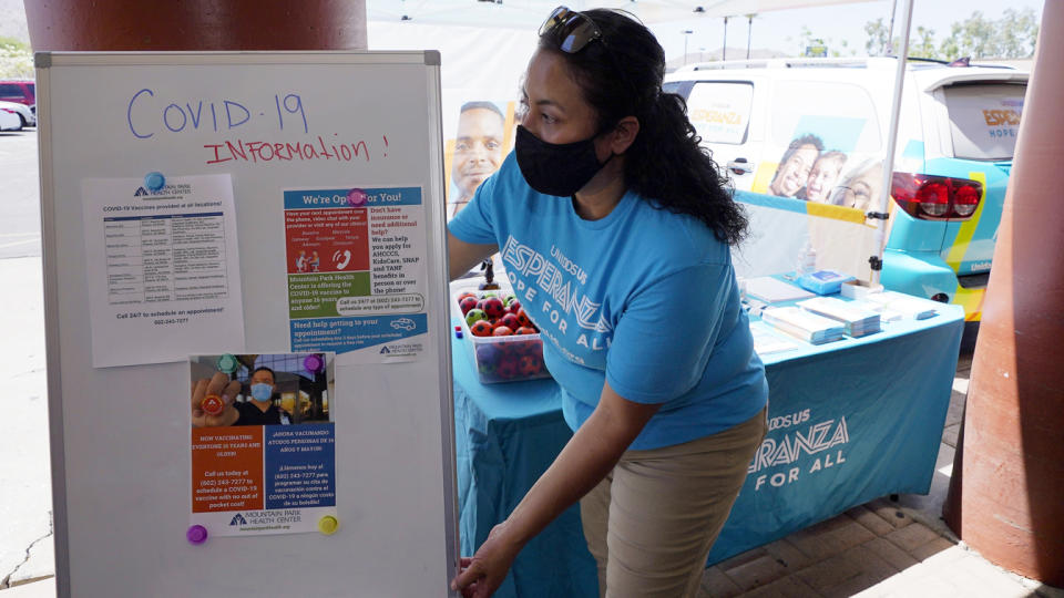 Sonia Lorenzana, of UnidosUS, sets up an informational tent to increase efforts to bring more vaccine doses into Latino neighborhoods at a local shopping plaza Friday, May 7, 2021, in Phoenix. (Ross D. Franklin/AP Photo)