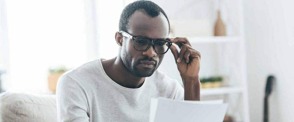 Man looking at piece of paper while holding glasses and sitting on the couch