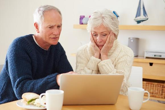 A worried senior couple examining Medicare plan costs on their laptop.