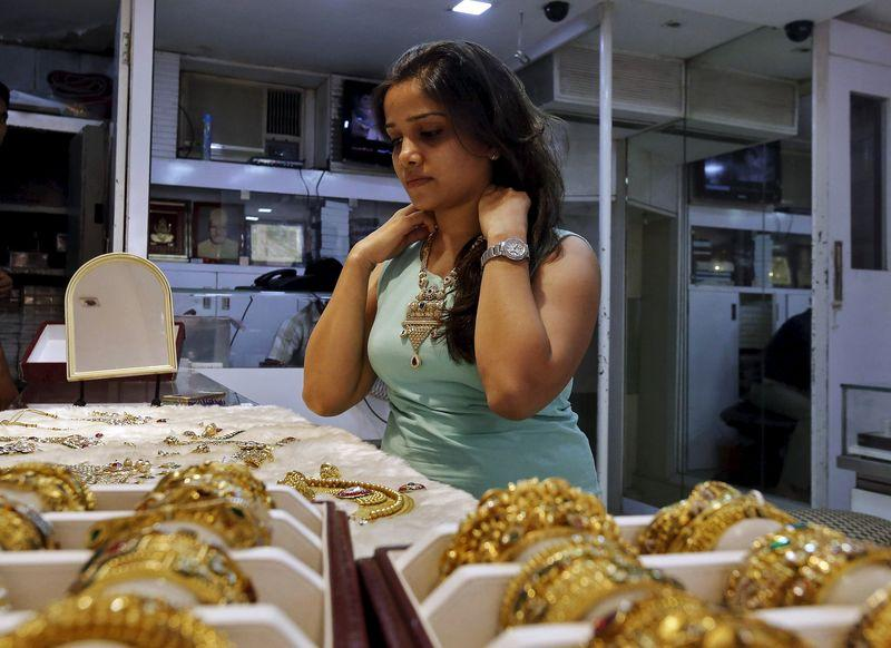 A woman tries on a gold necklace inside a jewellery showroom at a market in Mumbai