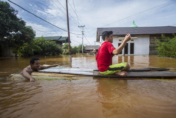 People use a makeshift raft to cross through a flooded village in Banjar, South Kalimantan on Borneo Island, Indonesia, in this Saturday, Jan. 16, 2021 photo. Many thousands of people have been evacuated and a number have been killed in recent days in flooding on Indonesia's Borneo island, officials said Sunday. (AP Photo/Putra)