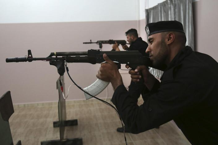 Palestinian security officers Ahed Abu Shabban, 23, foreground, and Muhmmad Debo, 22, aim electronically-modified AK-47 rifles at the headquarters of the security training department of the Hamas interior ministry in Gaza City, in the northern Gaza Strip on Thursday, April 10, 2014. The laser-fitted rifles are a money saver that eliminates the need to train with live ammunition, which is in short supply in Gaza. (AP Photo/Adel Hana)