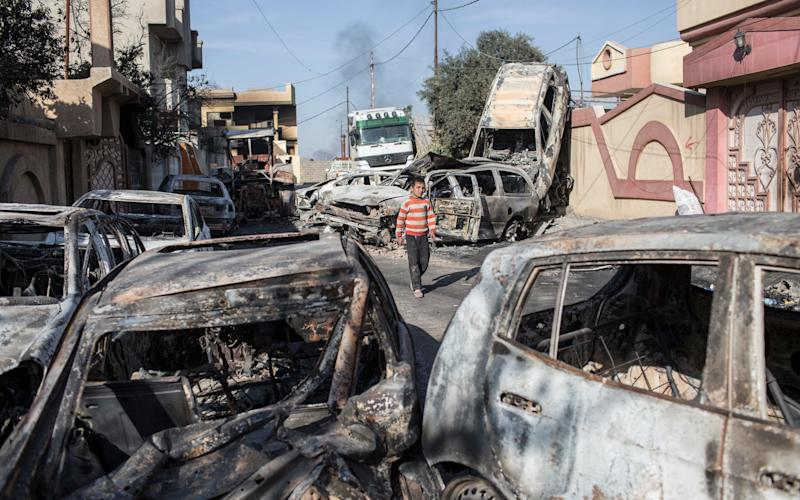 A boy walks past cars that were burned to create a smokescreen for ISIS fighters, in the neighbourhood of Sammod, on the southern edge of western Mosul, on March 9, 2017 - Credit: Sam Tarling / The Telegraph