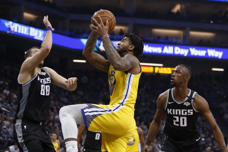 Golden State Warriors forward Marquese Chriss, center, goes to the basket between Sacramento Kings Nemanja Bjelica, left, and Harry Giles III, right, during the first quarter of an NBA basketball game in Sacramento, Calif., Monday, Jan. 6, 2020. (AP Photo/Rich Pedroncelli)