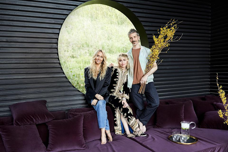 "Miley, with her mom, Tish Cyrus, and Tish's design partner Mat Sanders, take a moment in the backyard's luxe cabana, a new construction. Not your run-of-the-mill shelter from the sun, this cabana also doubles as an outdoor home theater fitted with a projector and retractable screen, blackout shades, heat for the winter, and misters for the summer. It was Sanders's idea to knock the hole out of the back wall. Says Tish, ""He asked, 'What if we could see through it and see green?' I was like, 'Oh, my gosh, yes!'"""