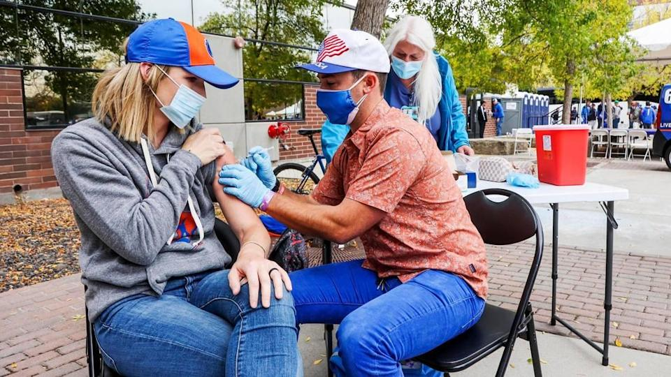Shalyn Blaisdell, of Kuna, receives a dose of COVID-19 vaccine from Boise State nursing program student Dane Larson outside Albertsons Stadium on Saturday. Boise State rewarded fans with prizes for being vaccinated and masking up.