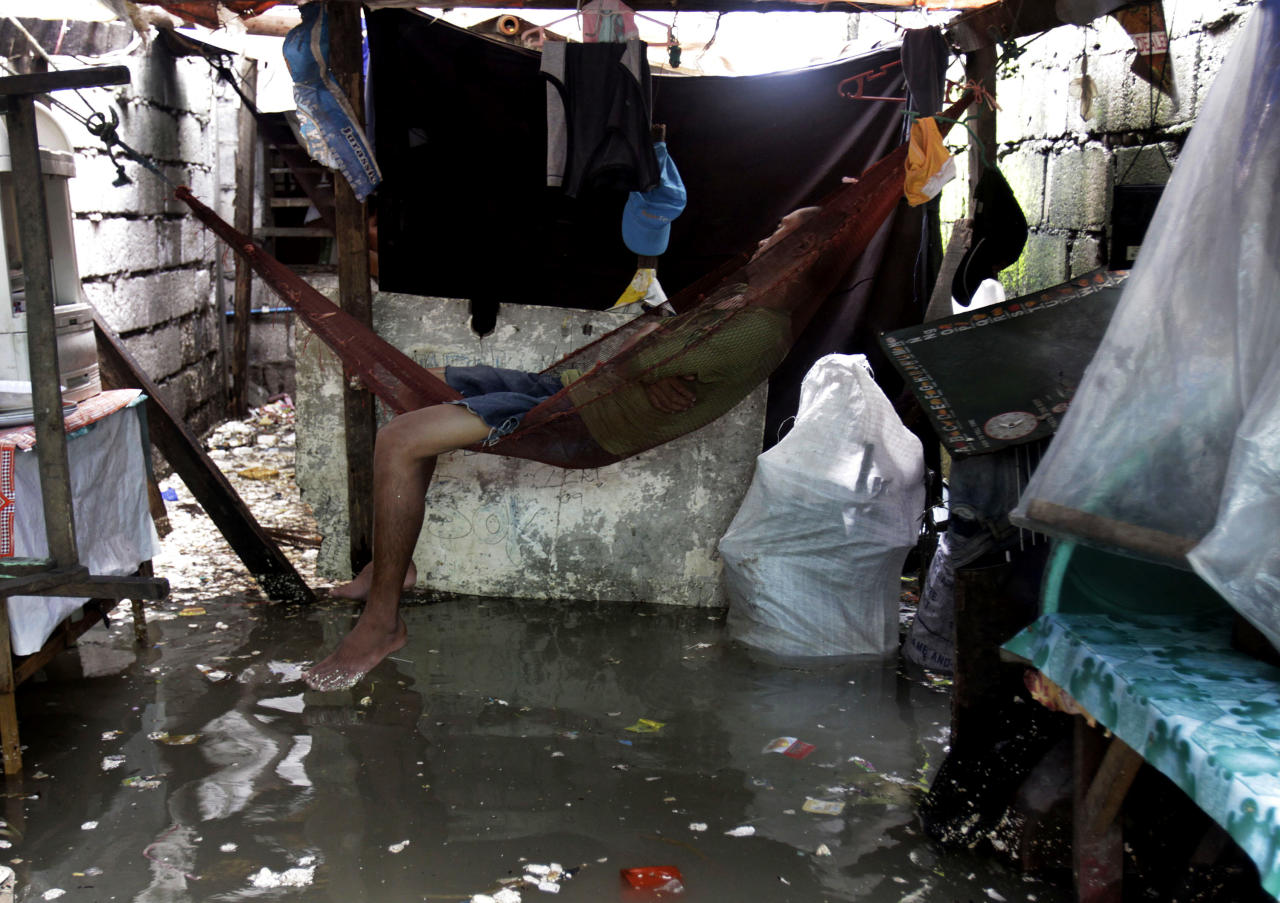 A man sleeps in a hmmock inside his house as flood waters continue to rise due to rains and high tide Thursday, Aug. 2, 2012 in Navotas City, north of Manila, Philippines. Exiting Typhoon Saola left nearly two dozens of people dead and forced 180,000 to flee their homes in the country. (AP Photo/Pat Roque)