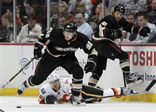 Calgary Flames right wing Jarome Iginla hits the ice as Anaheim Ducks defenseman Toni Lydman (32) goes after the puck in the second period of an NHL hockey game in Anaheim, Calif., on Monday, Feb. 6, 2012. A right is Ducks center Rod Pelley. (AP Photo/Christine Cotter)