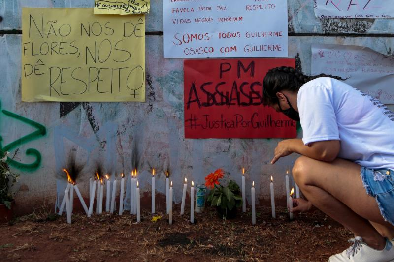 A woman lights a candle during a mass and a protest against the death of teenager Guilherme Silva Guedes, who disappeared in Vila Clara, Sao Paulo, Brazil, on June 21, 2020. (Photo by Miguel SCHINCARIOL / AFP) (Photo by MIGUEL SCHINCARIOL/AFP via Getty Images)