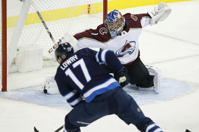 Winnipeg Jets' Adam Lowry's (17) shot is saved by Colorado Avalanche goaltender Semyon Varlamov (1) during the first period of an NHL hockey game, Friday, Nov. 9, 2018, in Winnipeg, Manitoba. (John Woods/The Canadian Press via AP)