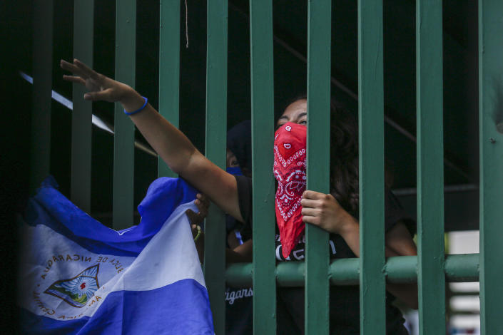 A masked student protests from behind the entrance gate of the Central American University (UCA) to demand the release of all political prisoners, on the last day of a 90-day period for releasing such prisoners as part of negotiations between the government and opposition, in Managua, Nicaragua, Tuesday, June 18, 2019. Nicaragua's government said Tuesday that it has released all prisoners detained in relation to 2018 anti-government protests, though the opposition maintains that more than 80 people it considers political prisoners are still in custody. (AP Photo/Alfredo Zuniga)