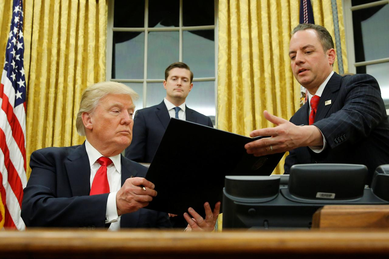 U.S. President Donald Trump hands Chief of Staff Reince Priebus (R) an executive order that directs agencies to ease the burden of Obamacare, after signing it in the Oval Office in Washington, U.S. January 20, 2017. Also pictured is White House Staff Secretary Rob Porter (C). REUTERS/Jonathan Ernst     TPX IMAGES OF THE DAY