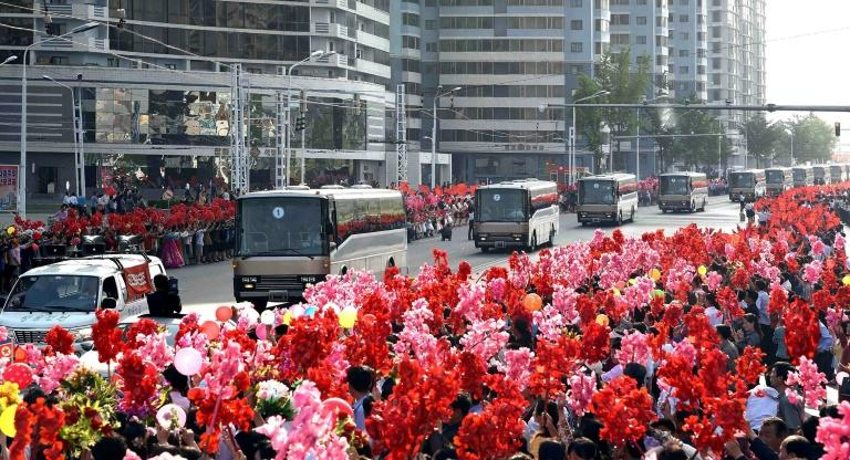 People greet buses carrying developers of the ground-to-ground medium-to-long range strategic ballistic rocket Hwasong-12 in Pyongyang on May 18, 2017