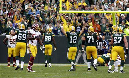 Green Bay Packers quarterback Aaron Rodgers (C) celebrates a touch down against the Washington Redskins during the first half of their NFL football game in Green Bay, Wisconsin September 15, 2013. REUTERS/Darren Hauck