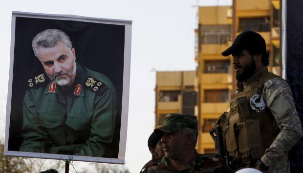 Soldiers hold a portrait of powerful Iranian commander Qassem Suleimani.