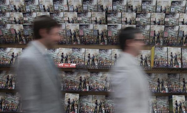 Jason Welker (L) and Scott Everhart walk past a wall full of X-Men comic books before their wedding ceremony at a comic book retail shop in Manhattan, New York June 20, 2012. A same-sex couple tied the knot at a comic book store in New York on Wednesday to celebrate the first gay nuptials in the superhero world in a new edition from Marvel Comics.