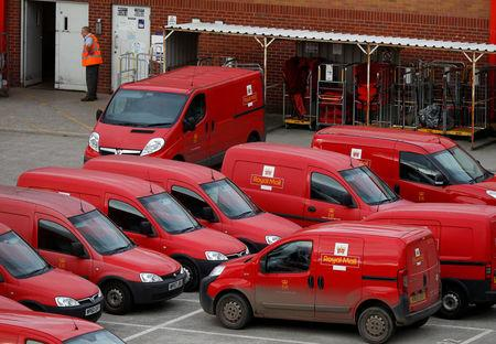 A Royal Mail postal worker stands in the yard of a sorting office in Altrincham