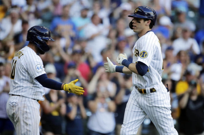 Milwaukee Brewers' Christian Yelich, right, is congratulated by Omar Narvaez after hitting a solo home run during the eighth inning of a baseball game against the Arizona Diamondbacks, Saturday, June 5, 2021, in Milwaukee. (AP Photo/Aaron Gash)