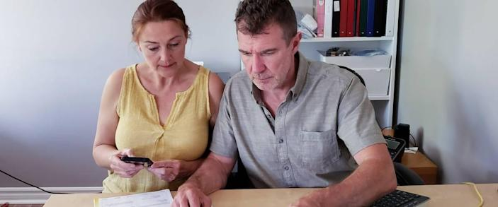 Couple look stressed, planning finances at their kitchen table.