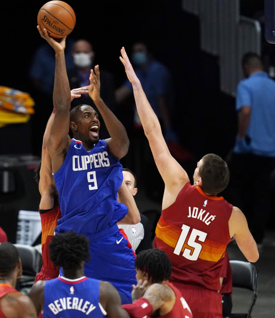 Los Angeles Clippers forward Serge Ibaka shoots over Denver Nuggets center Nikola Jokic during the first half of an NBA basketball game Friday, Dec. 25, 2020, in Denver. (AP Photo/David Zalubowski)