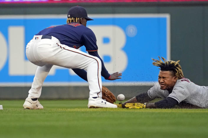 Cleveland Indians' Jose Ramirez, right, tries to stretch a single into a double as Minnesota Twins shortstop Nick Gordon reaches for the ball and tags Ramirez out during the first inning of a baseball game Wednesday, Sept. 15, 2021, in Minneapolis. (AP Photo/Jim Mone)