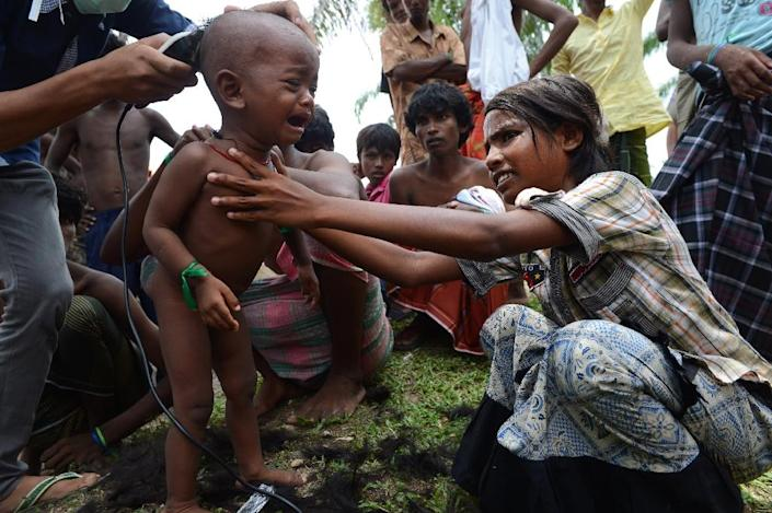 Rohingya children receive haircuts by Indonesian volunteers at the newly set up confinement area for migrants at Bayeun, in Indonesia's Aceh province on May 22, 2015 (AFP Photo/Romeo Gacad)
