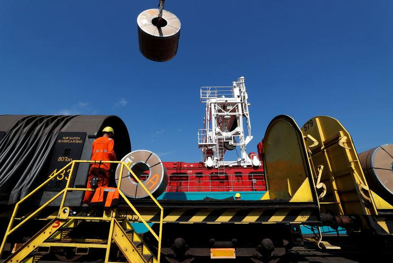 Metal coils are unloaded from a train at ArcelorMittal steel plant in Ghent