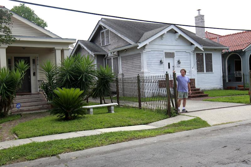 In this May 10, 2012 photo, homeowner Jim Provensal stand between his home, left, and a blighted home next door, which is managed by the Louisiana Land Trust, an agency set up to handle the wrecked properties using federal funds, in New Orleans. More than 3,000 lots flooded by Hurricane Katrina and bought with federal money in an emergency bailout sit idle across this city: a multimillion-dollar drain on federal, state and city coffers that lends itself to no easy solution. An Associated Press examination of the properties sold to the government by homeowners abandoning New Orleans after the catastrophic 2005 flood has found that about $86 million has been spent on handling a total of 5,100 abandoned parcels. And there's no end in sight to maintenance costs for perhaps most of the 3,100 properties that remain unsold. (AP Photo/Gerald Herbert)