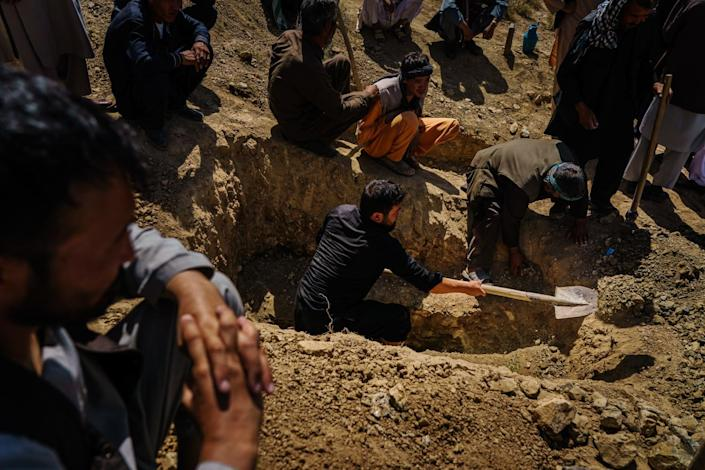 People dig a grave on a hillside.