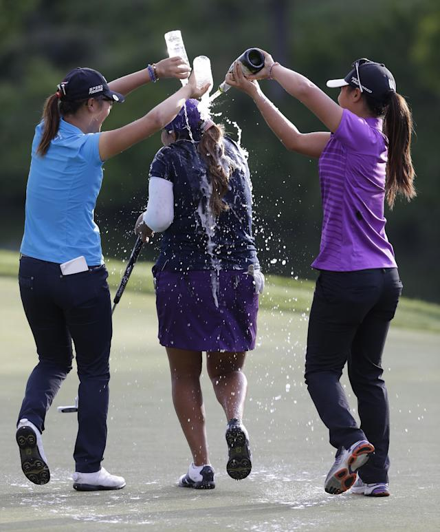 Lydia Ko, left, and Danielle Kang, right, douse Lizette Salas, with sparkling wine and water as she celebrates winning the Kingsmill Championship golf tournament at the Kingsmill resort in Williamsburg, Va., Sunday, May 18, 2014. Salas won her first LPGA event after shooting an even par-71 leaving her at 13-under for the tournament. (AP Photo/Steve Helber)