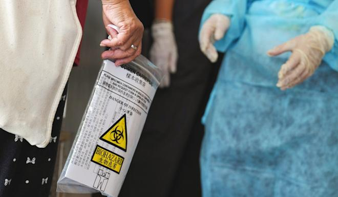 A saliva sample from a resident is collected for testing on Tuesday. Photo: Sam Tsang