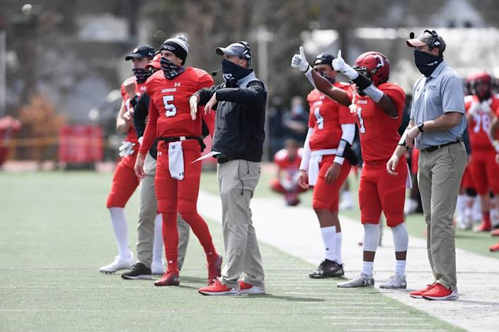 Davidson coach Scott Abell (center, in black) signals to his team during a game against Presbyterian in March. Abell and his staff have turned the program around since arriving in 2018, in part by relying on a spread option, run-heavy offense.
