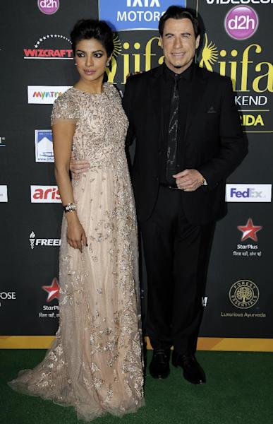 Indian film star Priyanka Chopra, left, poses with actor John Travolta as they walk the green carpet during the arrival for 15th annual International Indian Film Awards Saturday, April 26, 2014, in Tampa, Fla. (AP Photo/Chris O'Meara)
