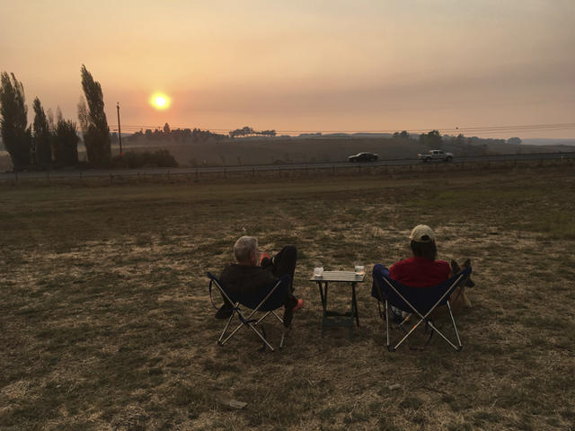 <p>Evacuees Ron Vitt, 75, left, and Ellen Brantley, 65, enjoy an evening at Sonoma Raceway sipping wine as smoke from several wildfires fills the sky Friday, Oct. 13, 2017, in Sonoma, Calif. They celebrated their 29th anniversary Sunday, Oct. 8. Their home is okay, so far. (Photo: Janie Har/AP) </p>