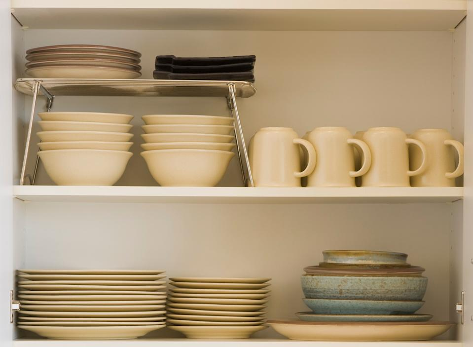 Kitchen countertop with open cupboard with stacks of dishes, bowls, and cups.