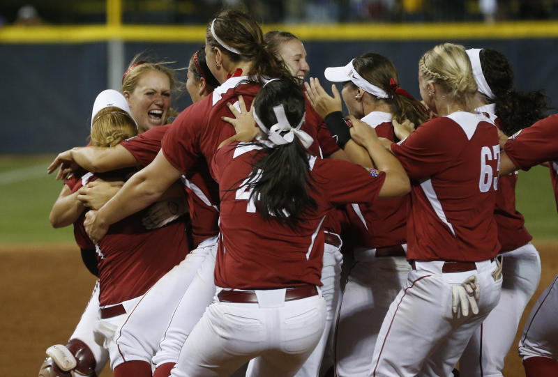 CORRECTS SCORE TO 4-0-Oklahoma catcher Jessica Shults, second from left, hugs pitcher Michelle Gascoigne, left, back to camera, as the team rushes out the the pitching circle as Oklahoma defeats Tennessee in the seventh inning of the second game of the best of three Women's College World Series NCAA softball championship series in Oklahoma City, Tuesday, June 4, 2013. Oklahoma won the game 4-0 and the best of three series in two games.(AP Photo/Sue Ogrocki)