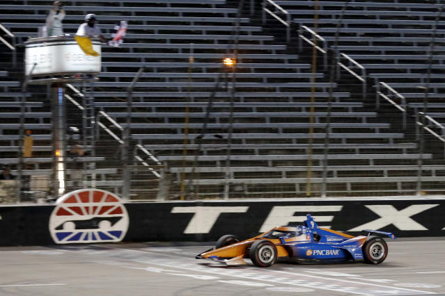 Scott Dixon earns the checkered flag as he crosses the finish line to win an IndyCar auto race at Texas Motor Speedway in Fort Worth, Texas, Saturday, June 6, 2020. (AP Photo/Tony Gutierrez)