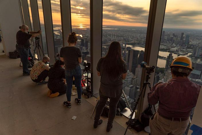 Amateur astronomers watch as the sun rises partially eclipsed in New York City.