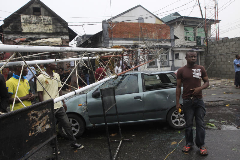 People gather around a car that was smash by a telecom mast  following a storm in Lagos, Nigeria, Monday, Feb. 13, 2012. A sudden storm has torn through Nigeria's commercial capital, killing at least one person. The storm Monday morning brought torrential rains and incredibly strong winds through Lagos' islands. An Associated Press journalist saw the corpse of one man on Ikoyi Island, apparently killed when a fixed antennae tore away from its cement base and struck him in the head.(AP Photo/Sunday Alamba)