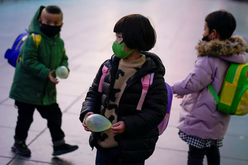 FILE PHOTO: Children wearing face masks are seen at Shanghai railway station as the country is hit by an outbreak of the novel coronavirus, in Shanghai