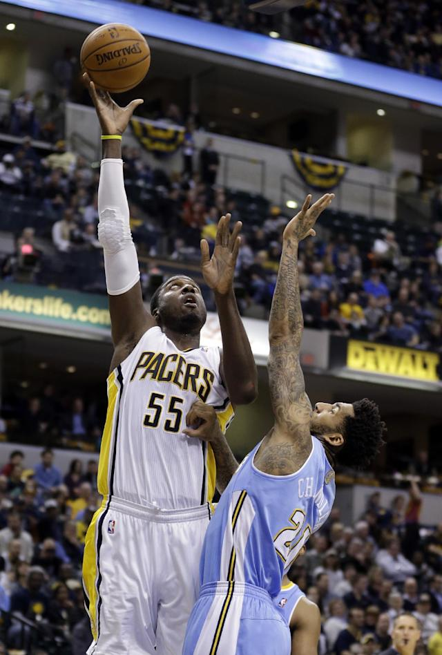 Indiana Pacers center Roy Hibbert (55) shoots over Denver Nuggets forward Wilson Chandler in the second half of an NBA basketball game in Indianapolis, Monday, Feb. 10, 2014. The Pacers won 119-80. (AP Photo/Michael Conroy)