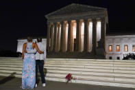 A couple pauses outside the Supreme Court Friday, Sept. 18, 2020, in Washington, after the Supreme Court announced that Supreme Court Justice Ruth Bader Ginsburg has died of metastatic pancreatic cancer at age 87. (AP Photo/Alex Brandon)