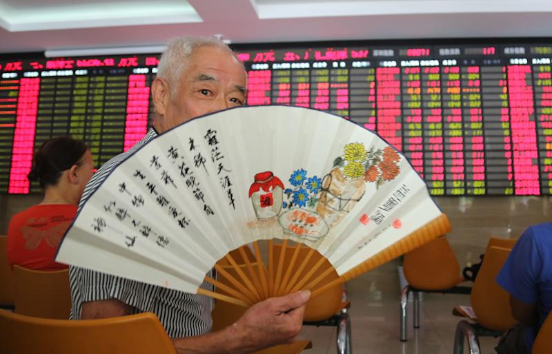 An investor cools off with a fan at a private securities company on Tuesday July 9, 2013 in Shanghai, China. Asian stock markets rebounded Tuesday, joining a global rally following positive U.S. economic news as nervousness about an imminent scaling back of the Federal Reserve's monetary stimulus eased. China's Shanghai Composite rose 0.3 percent to 1,963.27. (AP Photo)