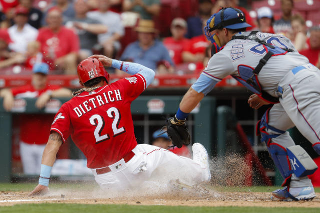 Cincinnati Reds' Derek Dietrich (22) scores against Texas Rangers catcher Tim Federowicz, right, in the third inning of a baseball game, Sunday, June 16, 2019, in Cincinnati. (AP Photo/John Minchillo)